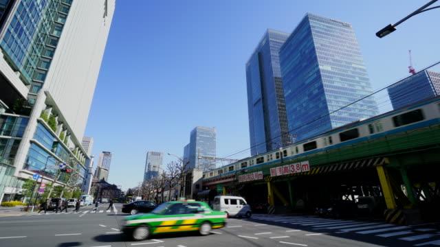 cars run under elevated train at marunouchi. - タクシー点の映像素材/bロール