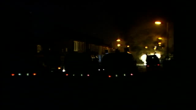 Cars set alight during riots in Northern Ireland NORTHERN IRELAND Belfast Crumlin Road EXT Armoured police Land Rovers in line across road as...