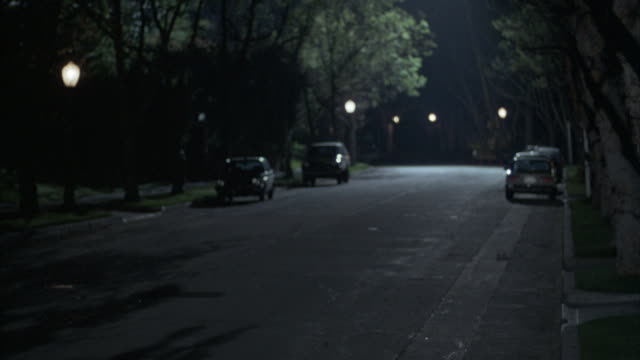 Cars sit parked on a dark residential street.