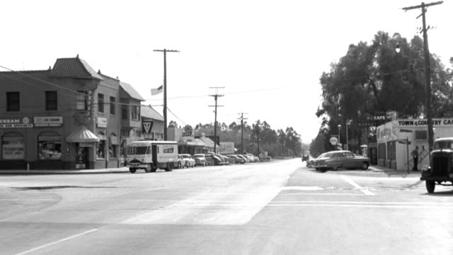 cars slow at a traffic intersection and then turn down a street in a small town. - 1958 stock videos & royalty-free footage