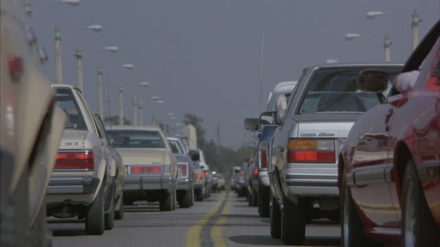 Cars slowly move in a traffic jam.