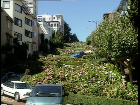 cars slowly negotiate steep bends in lombard street as they zig zag towards camera pedestrians cross in foreground - lombard street san francisco stock videos & royalty-free footage