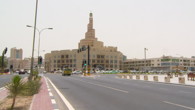 cars speed through intersection in front of interesting architectural building under grey sky - doha, qatar - doha stock videos & royalty-free footage