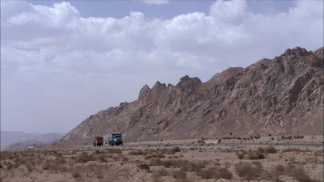 ws pan cars speeding across desert highway, iran - iran stock videos & royalty-free footage