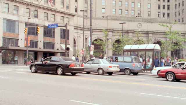 cars stop for traffic in front of  a bus stop near public square in cleveland, ohio. - courtyard stock videos & royalty-free footage