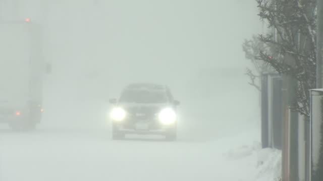 cars stopping in blizzard, hokkaido, japan - 通路点の映像素材/bロール
