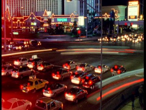 cars stream across street at night, las vegas - las vegas crosses stock-videos und b-roll-filmmaterial
