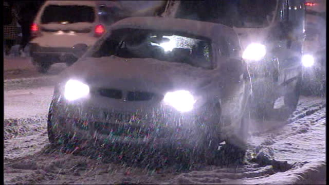 cars stuck in snow blizzard as one car slides on road people pushing snow covered car off road - rutschen stock-videos und b-roll-filmmaterial