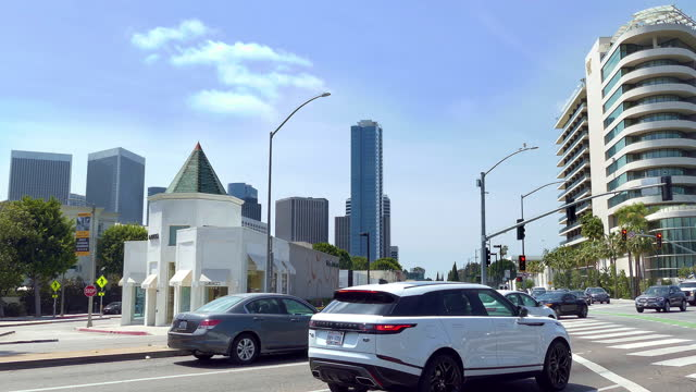los angeles, california, usa - april 6, 2021: cars traffic on wilshire boulevard near waldorf astoria beverly hills hotel and century city skyline in los angeles, california, 4k - century city stock videos & royalty-free footage