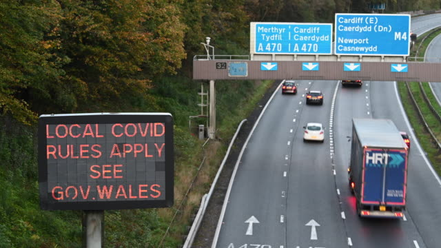 """cars travel on the m4 motorway at radyr near a motorway sign which says """"local covid rules apply"""" on october 12 in cardiff, wales. first minister of... - regole video stock e b–roll"""