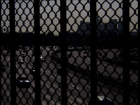cars travel round bend in freeway viewed through chain-link fence los angeles - chainlink fence stock videos and b-roll footage