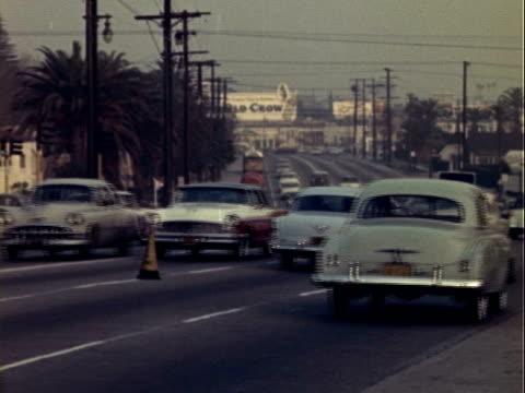 cars traveling along busy eight lane street or highway traffic scene 1950s on january 01 1950 in los angeles california - 1950年点の映像素材/bロール