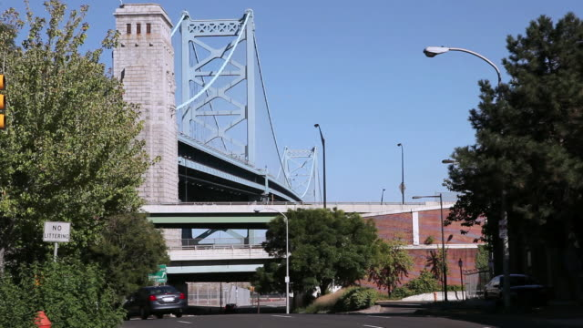 la cars traveling in the city along and under overpasses with the benjamin franklin bridge in the distance / philadelphia, pennsylvania, united states - ベンフランクリン橋点の映像素材/bロール