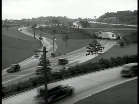cars traveling on winding highway & access roads w/ houses suburbs distant bg. steel girder suspension & manhattan bridge. george washington bridge. - マンハッタン橋点の映像素材/bロール