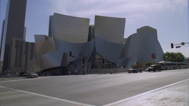 ws cars traveling past the stainless steel paneled walt disney concert hall / los angeles, california, united states - concert hall stock videos and b-roll footage