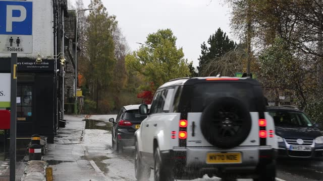 cars travelling too fast through large puddles and soaking a pedestrian in ambleside, lake district, uk - disrespect stock videos & royalty-free footage