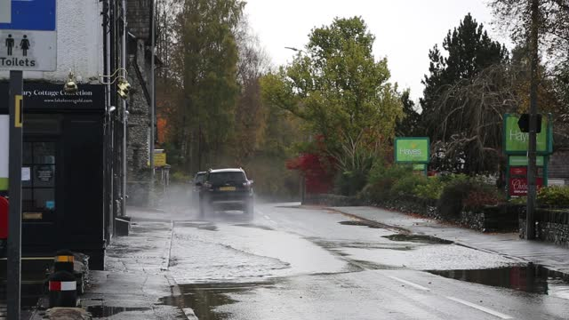 cars travelling too fast through large puddles and soaking the adjacent houses in ambleside, lake district, uk. - disrespect stock videos & royalty-free footage
