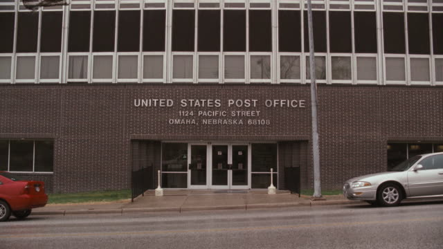 cars, trucks, and vans drive past the us post office in omaha. - postamt stock-videos und b-roll-filmmaterial
