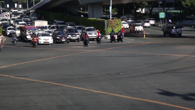 Cars turn while pedestrians walk along a crossing in the Makati district of Manila the Philippines on Monday Nov 16 Pedestrians cross a road at a...