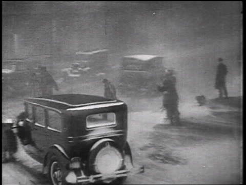b/w 1935 cars turning corner + pedestrian crossing street in snowstorm / educational - 1935 stock videos & royalty-free footage