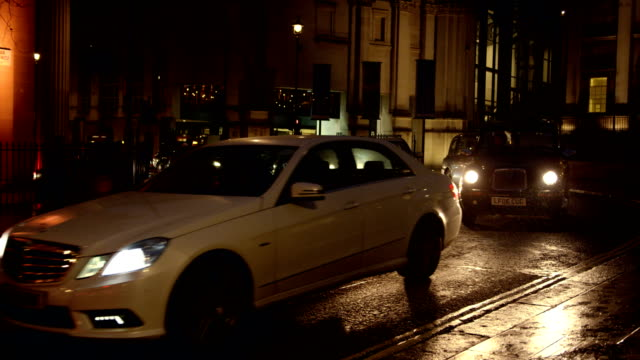 Cars turning to Trafalgar square in London in slow motion at night on rain.