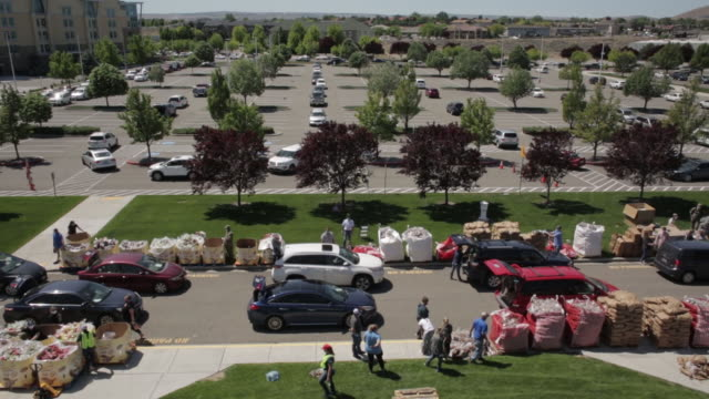 cars wait in line for handouts of surplus potatoes and other free items including milk grains produce bacon and more in kennewick washington us on... - sharing stock videos & royalty-free footage