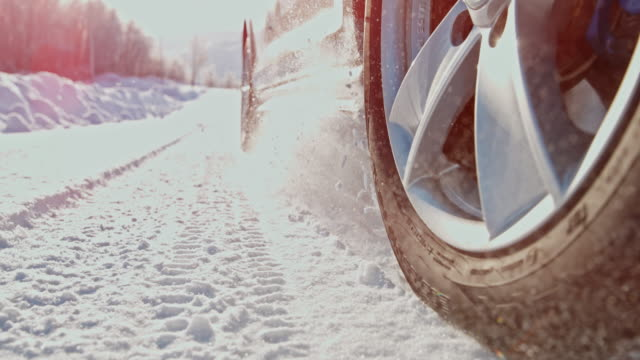 slo mo car's wheel spinning in the snow - slippery stock videos and b-roll footage