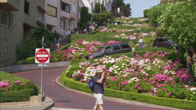 cars zigzag down san francisco's lombard street. - lombard street san francisco stock videos & royalty-free footage