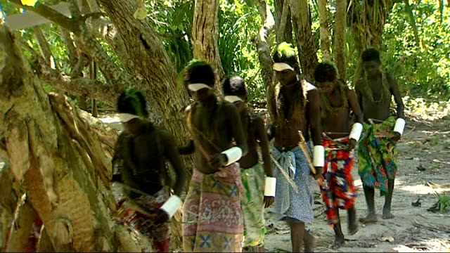 han island young men wearing sarongs and protective white bandages on one forearm carrying wooden bows and arrows / close up on some with white paint... - forearm stock videos and b-roll footage