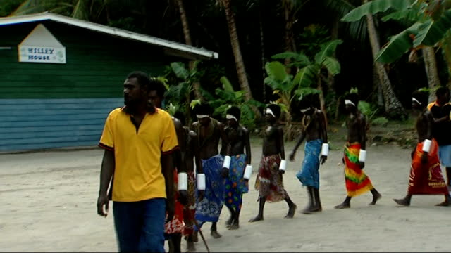 huene island papua new guinea carteret islands huene island ext young male islanders wearing colourful sarongs and fern leaves on their heads walk... - パレオ点の映像素材/bロール