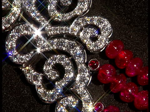 Cartier jewellery Closeup of Cartier silver necklace and sparkling diamonds / Red ruby bead necklace with diamonds / Glamorous diamond necklace with...