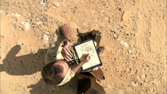 a cartographer looks through binoculars as he draws a sketch in the sahara desert. - cartography stock videos & royalty-free footage