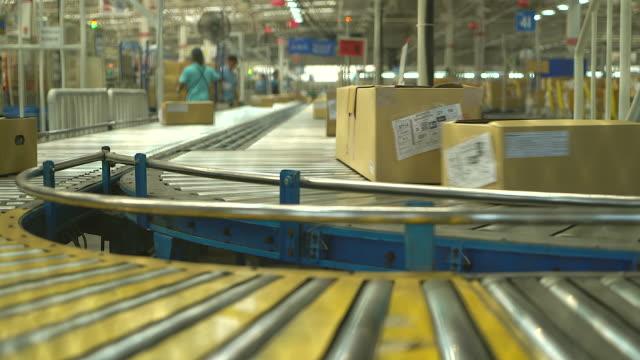 scatola di cartone che si muove su rulli trasportatori. - box container video stock e b–roll