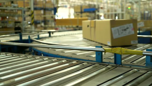 vídeos de stock e filmes b-roll de carton box moving on conveyor rollers. - correia transportadora
