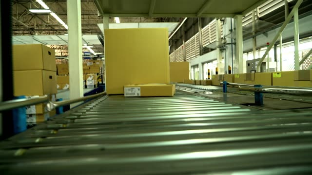 carton box moving on conveyor rollers. - conveyor belt stock videos & royalty-free footage