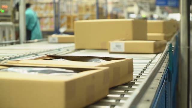 カートンは、オンラインショッピングや手作業を削減する自動化を伴う仕事に適用可能な、業界のコンベアベルトで運ばされています。そして機械に置き換えられる - コンベヤーベルト点の映像素材/bロール