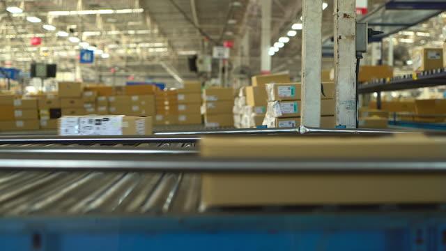 kartons werden in der branche auf einem förderband transportiert, das für aufträge mit online-shopping oder automatisierung geeignet ist, die den manuellen arbeitsaufwand reduzieren. und ersetzt durch maschinen - lagerhalle stock-videos und b-roll-filmmaterial