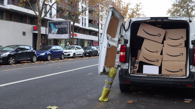 cartons with the amazon logo are stored in the trunk of a utility vehicle, pending delivery. amazon is an american e-commerce company based in... - gafam stock-videos und b-roll-filmmaterial