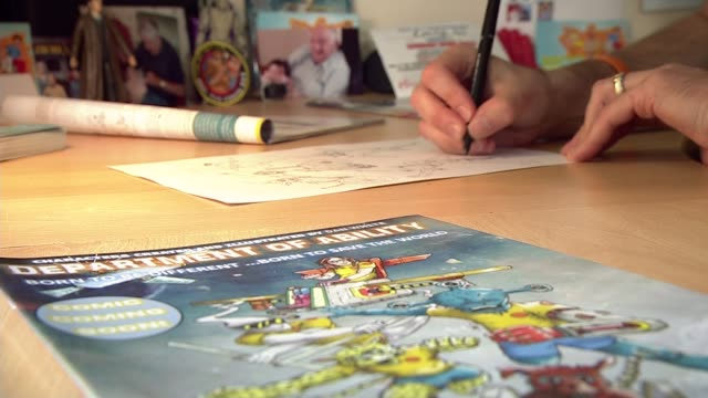 cartoonist inspired by daughter with spina bifida creates comic strip where disabled superheroes save the world; various shots of dan white drawing... - カトゥーニスト点の映像素材/bロール