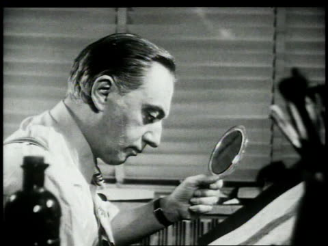 cartoonist looking in mirror / looking at own reflection in mirror / drawing his expression in comic strip - cartoonist stock videos & royalty-free footage
