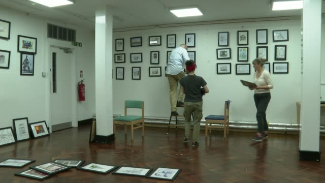 exhibition of cartoons looks at life in london england london charing cross charing cross library int various shots of cartoons being hung in library... - charing cross stock videos and b-roll footage