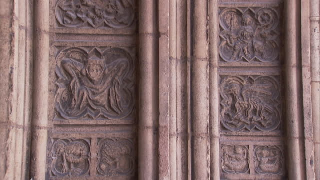 Carved frescoes fill the space between columns at the entrance to the Lyon Cathedral.