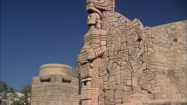 vídeos de stock, filmes e b-roll de a carved totem decorates the engraved exterior of a bandera monument in merida, yucatan, mexico. - yucatán
