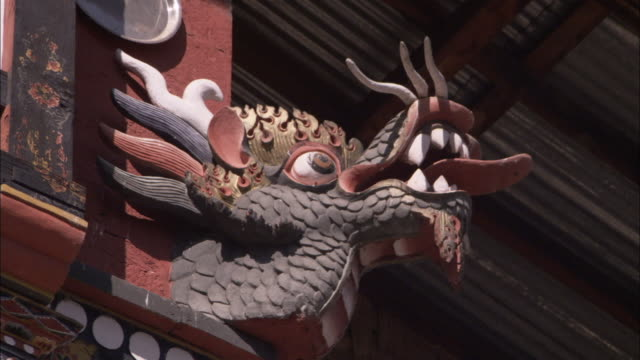 carved wooden dragons are located on the eaves of the national library of thimpu available in hd - eaves stock videos and b-roll footage