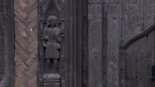 a carving flanks the entrance of a medieval cottage. available in hd. - lavenham stock-videos und b-roll-filmmaterial