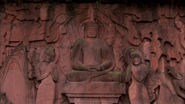 a carving of buddha surrounded by priests. available in hd. - buddha stock-videos und b-roll-filmmaterial