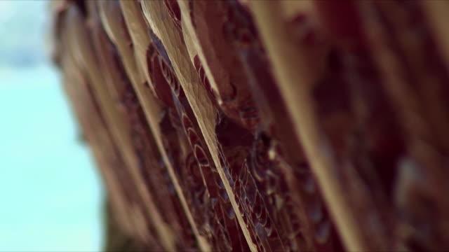 ecu selective focus carving on side of boat, waitangi, northland, new zealand - ニュージーランド べイ・オブ・アイランズ点の映像素材/bロール