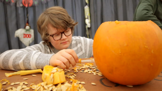 carving pumpkins is fun! - only teenage boys stock videos & royalty-free footage