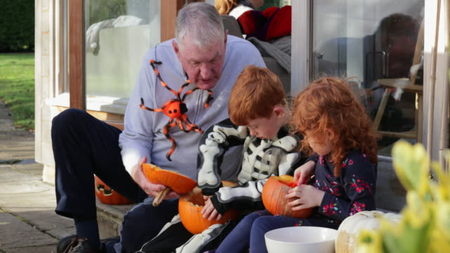 carving pumpkins with grandpa - jack o' lantern stock videos and b-roll footage