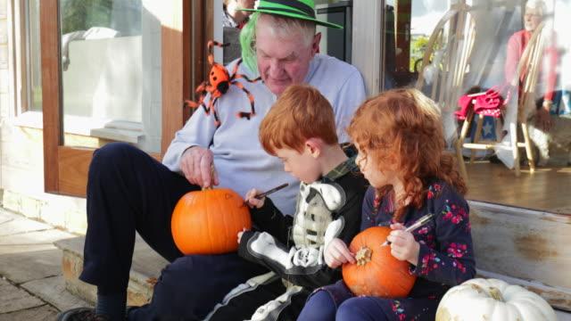 vídeos de stock e filmes b-roll de carving pumpkins with grandpa - arte e artesanato arte visual